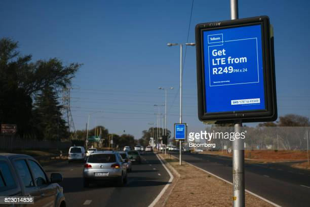 Vehicles pass advertising signs for mobile phone deals from Telkom SA SOC Ltd on a road in Pretoria South Africa on Tuesday July 25 2017 South Africa...