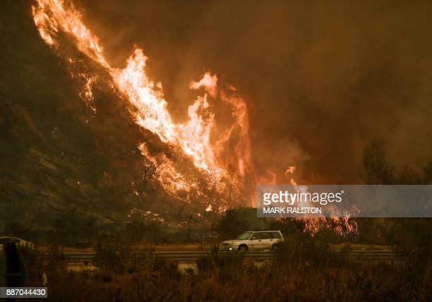 TOPSHOT Vehicles pass beside a wall of flames on the 101 highway as it reaches the coast during the Thomas wildfire near Ventura California on...