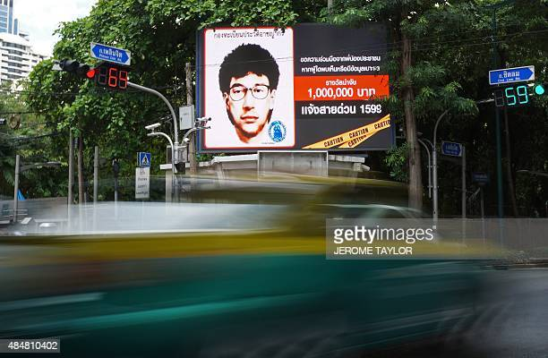 Vehicles pass by a digital billboard showing the sketch of a man suspected to be the Bangkok bomber in central Bangkok on August 22 2015 The son of...