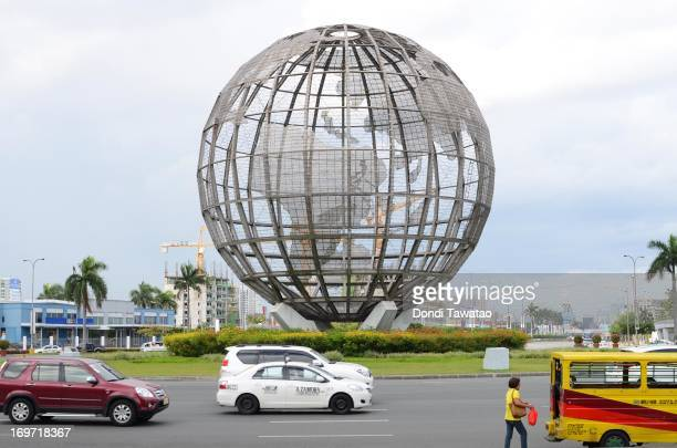 Vehicles pass by a steel globe structure at a mall on May 31 2013 in Manila Philippines The Philippines had the fastestgrowing economy among Asian...