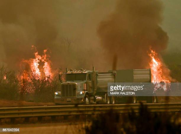 Vehicles pass by a wall of flames as they drive on the 101 highway during the Thomas wildfire near Ventura California on December 6 2017 California...