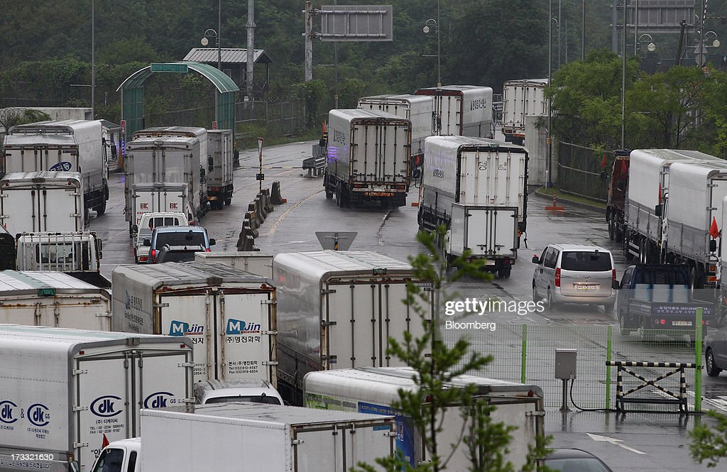 Vehicles pass the Customs, Immigration and Quarantine (CIQ) office as they travel toward the Gaeseong Industrial Complex, on a road linked to North Korea, near the demilitarized zone (DMZ) in Paju, South Korea, on Friday, July 12, 2013. North Korea notified South Korea today that it has deferred two separate sets of talks on the tours and the family reunions it proposed yesterday, and said it wants to focus on the ongoing dialog to reopen the joint Gaeseong industrial zone, the Souths Unification Ministry said in an e-mailed statement. The two sides yesterday decided to hold talks in Gaeseong on July 15, which will be their third round in one week, on normalizing operations in Gaeseong after the North unilaterally recalled its workers in April. Photographer: SeongJoon Cho/Bloomberg via Getty Images