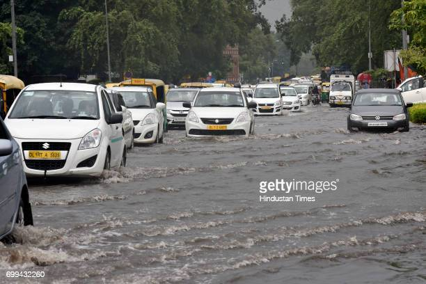 Vehicles pass through a waterlogged street at Baba Kharak Singh Marg on June 21 2017 in New Delhi India