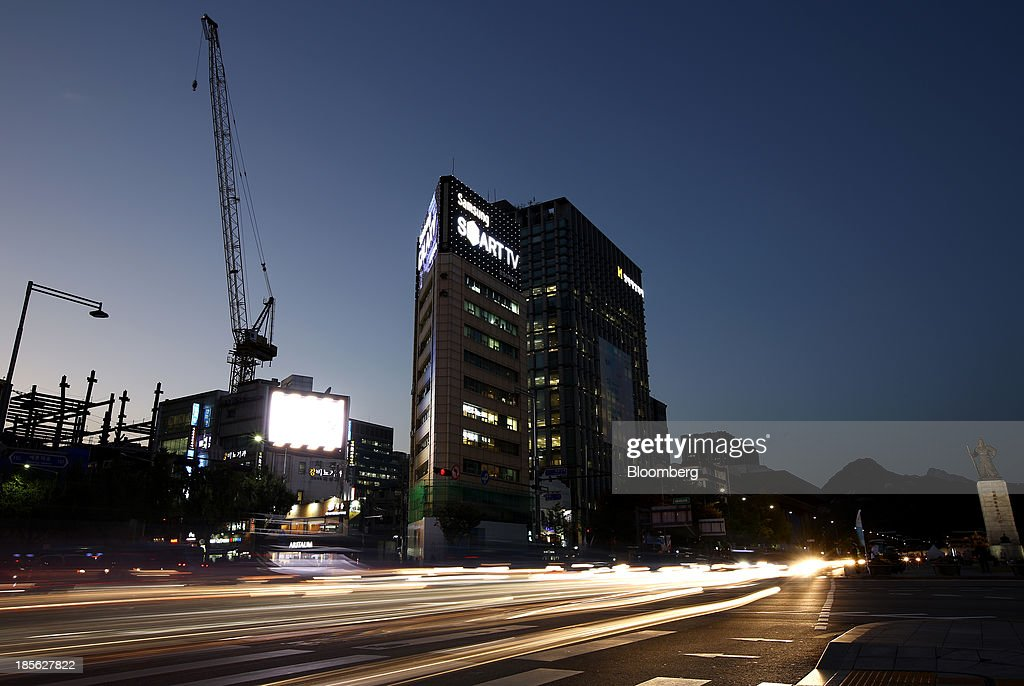 Vehicles pass through Gwanghwamun Square as a Samsung Electronics Co. advertisement is illuminated in the background in this long-exposure photograph taken in Seoul, South Korea, on Tuesday, Oct. 22, 2013. Samsung Electronics is scheduled to release third-quarter earnings on Oct. 25. Photographer: SeongJoon Cho/Bloomberg via Getty Images