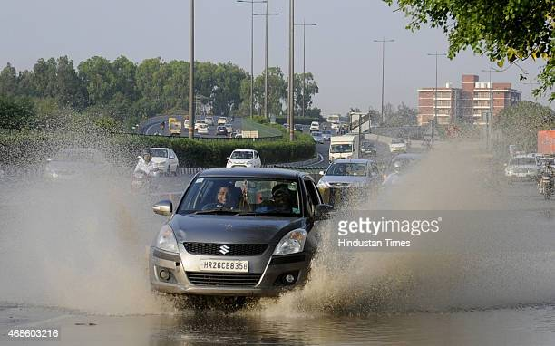 Vehicles passing through water logging after the post morning rains near Signature tower Chowk on April 4 2015 in Gurgaon India Heavy rainfall lashed...