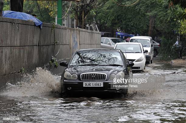 Vehicles passing through water logging after the post morning rains at Jangpura on April 4 2015 in New Delhi India Heavy rainfall lashed the National...