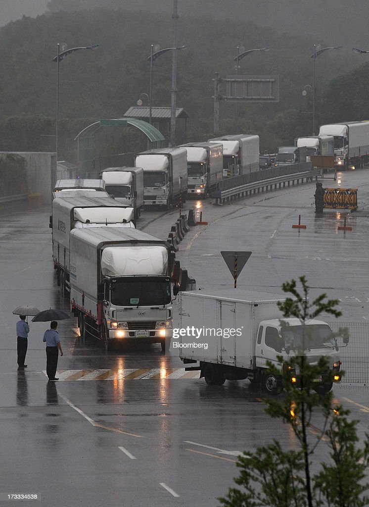 Vehicles returning from the Gaeseong Industrial Complex wait in line on a road linked to North Korea towards the Customs, Immigration and Quarantine (CIQ) office near the demilitarized zone (DMZ) in Paju, South Korea, on Friday, July 12, 2013. North Korea notified South Korea today that it has deferred two separate sets of talks on the tours and the family reunions it proposed yesterday, and said it wants to focus on the ongoing dialog to reopen the joint Gaeseong industrial zone, the Souths Unification Ministry said in an e-mailed statement. The two sides yesterday decided to hold talks in Gaeseong on July 15, which will be their third round in one week, on normalizing operations in Gaeseong after the North unilaterally recalled its workers in April. Photographer: SeongJoon Cho/Bloomberg via Getty Images