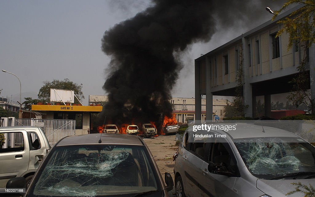 Vehicles set fire by the angry mob as they protest during the two-day nationwide strike called by various trade unions to protest against Government's economics and labour policies, on February 20, 2013 in Noida, India. Protest turned violent at Phase II in Noida as protesters pelted stones at factories and set seven to eight vehicles on fire.