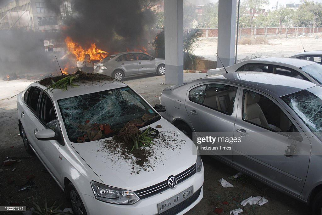 Vehicles set fire by the angry mob as they protest during the two-day nationwide strike called by various trade unions to protest against Government's economics and labour policies, on February 20, 2013 in Noida, India.Protest turned violent at Phase II in Noida as protesters pelted stones at factories and set seven to eight vehicles on fire.