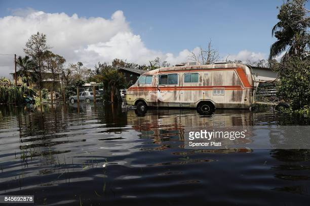 Vehicles stand in a flooded street in a rural part of Naples the morning after Hurricane Irma swept through the area on September 11 2017 in Naples...