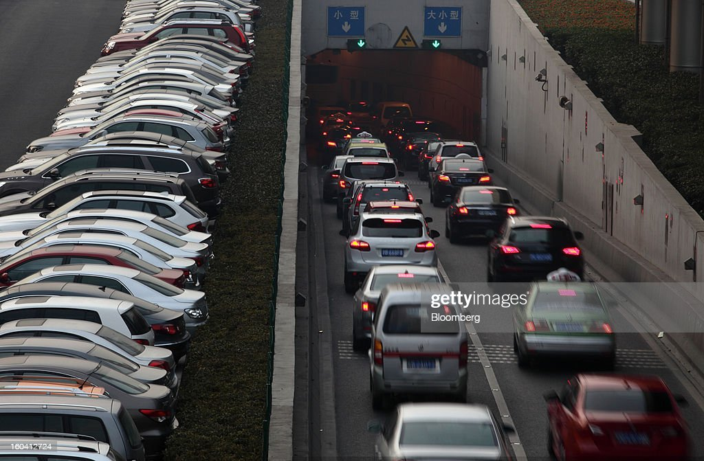 Vehicles stand in a parking lot, left, as traffic moves towards a tunnel in the Pudong area of Shanghai, China, on Wednesday, Jan. 30, 2013. China's economic growth accelerated for the first time in two years as government efforts to revive demand drove a rebound in industrial output, retail sales and the housing market. Photographer: Tomohiro Ohsumi/Bloomberg via Getty Images