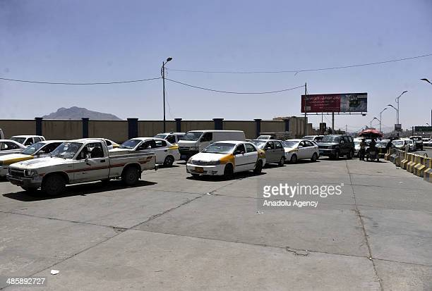 Vehicles stand in queues to fill fuel at a petrol station on April 21 2014 in Sanaa Yemen as the country sufferes from fuel shortages