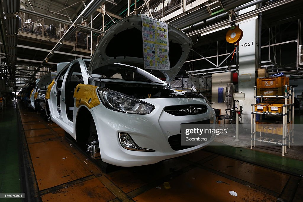 Vehicles stand on the halted assembly line at the Hyundai Motor Co. plant during a strike by the company's labor union in Ulsan, South Korea, on Tuesday, Aug. 20, 2013. Union members at Hyundai Motor, South Korea's largest automaker, staged a partial strike today that will continue tomorrow as they demand higher wages amid increasing competition with Japanese carmakers. Photographer: SeongJoon Cho/Bloomberg via Getty Images