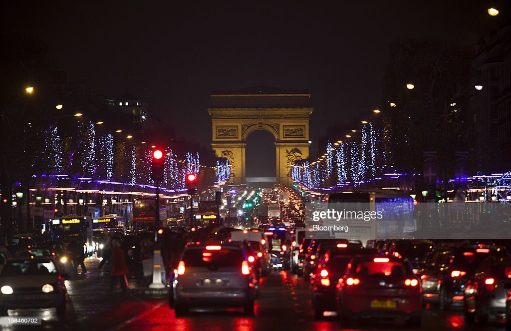 Vehicles stand stationary at traffic lights on the Champs-Elysees near the Arc de Triomphe national monument in Paris, France, on Saturday, Dec. 15, 2012. The French minister for energy and environment unveiled a proposal for lights in and outside shops, offices, and public buildings -- including the flagship Louis Vuitton store and the Lido cabaret house on Paris's Avenue des Champs Elysees -- to be turned off between 1 a.m. and 7 a.m. starting in July. Photographer: Balint Porneczi/Bloomberg via Getty Images