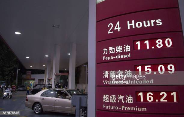 Vehicles stand while being refueled beyond a sign listing prices for various grades of fuel at a PetroChina Co gas station at night in Hong Kong...