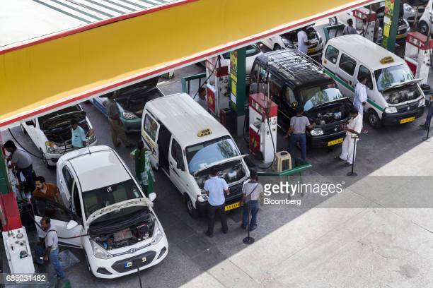 Vehicles stand while being refueled with compressed natural gas at an Indraprastha Gas Ltd gas station in New Delhi India on Wednesday May 17 2017...
