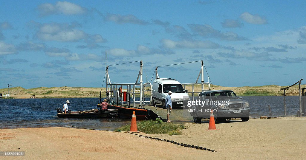 Vehicles start driving after being transported on a raft across Garzon Lagoon, from Rocha department to Maldonado department, Uruguay on December 27, 2012. AFP PHOTO/Miguel ROJO