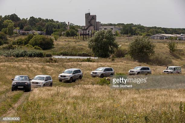Vehicles transporting observers from the Organization for Security and Cooperation in Europe drive through the main crash site of Malaysia Airlines...