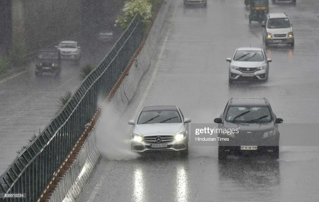 Vehicles wade through waterlogged road during the heavy rains at sector 18, on August 19, 2017 in Noida, India. Delhi received showers early morning which brought temperatures down to a comfortable 26 degrees Celsius. The India Meteorological Department (Met) officials said that there might be thunderstorm with showers later in the day while the maximum temperature is likely to be around 34 degrees Celsius.
