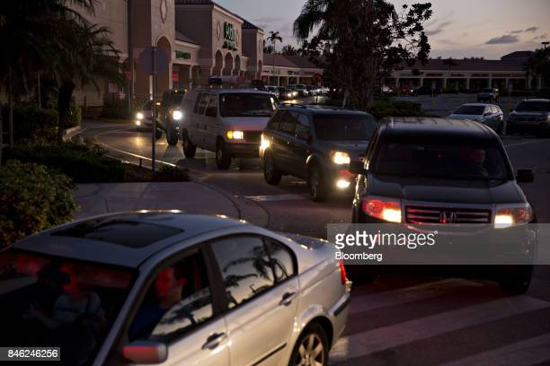 Vehicles wait in line to get fuel near a gas station in Estero Florida US on Tuesday Sept 12 2017 Seven million utility customers across the US...
