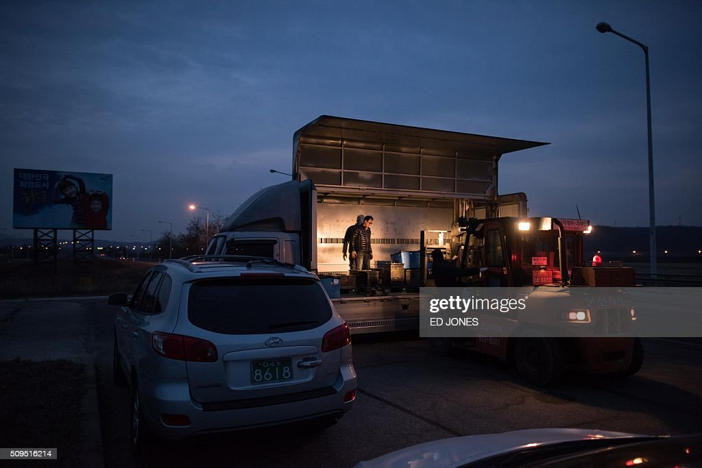 Vehicles which arrived from the Kaesong joint industrial area are offloaded on a roadside after a checkpoint near the Demilitarized Zone (DMZ) separating the two Koreas in Paju on February 11, 2016. North Korea on February 11 expelled all South Koreans from the jointly-run Kaesong industrial zone and seized their factory assets, saying Seoul's earlier decision to shutter the complex had amounted to a 'declaration of war'. AFP PHOTO / Ed Jones / AFP / ED JONES