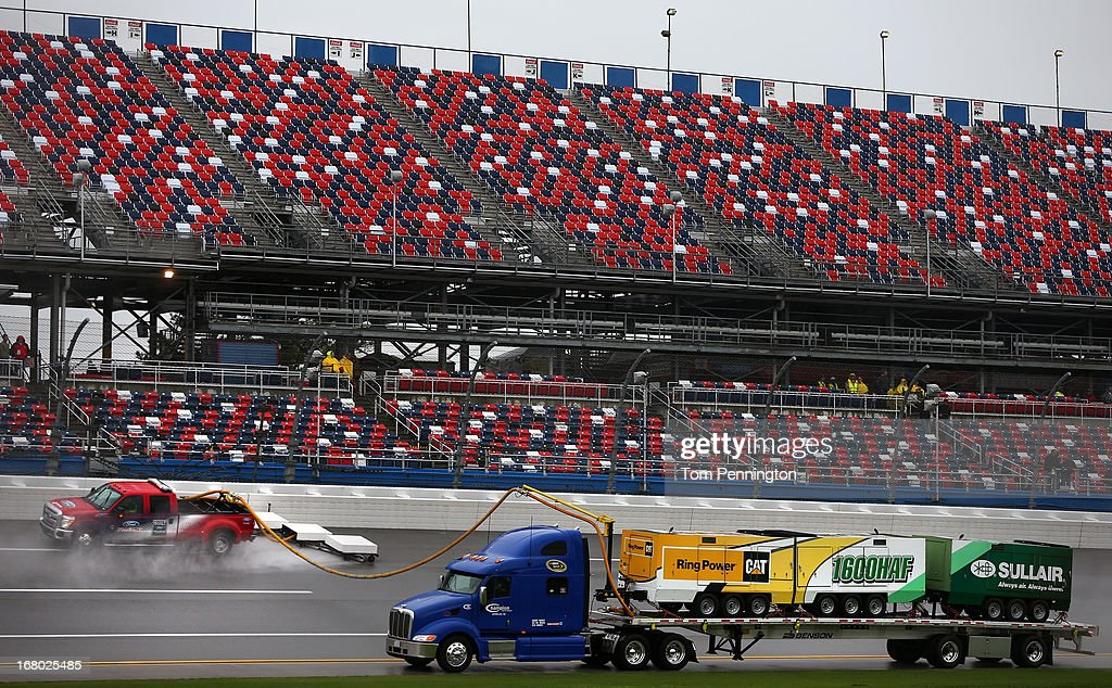 Vehicles with the NASCAR Air Titan drying machines attempt to dry the track after qualifying was canceled for the NASCAR Sprint Cup Series Aaron's 499 at Talladega Superspeedway on May 4, 2013 in Talladega, Alabama.