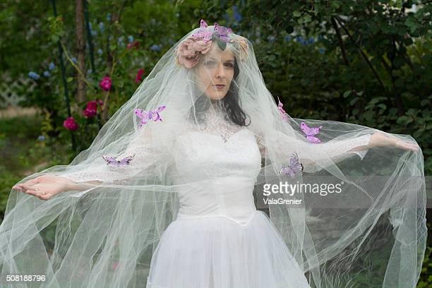 Nascosta sposa con braccia in fuori, ricoperta di farfalle.