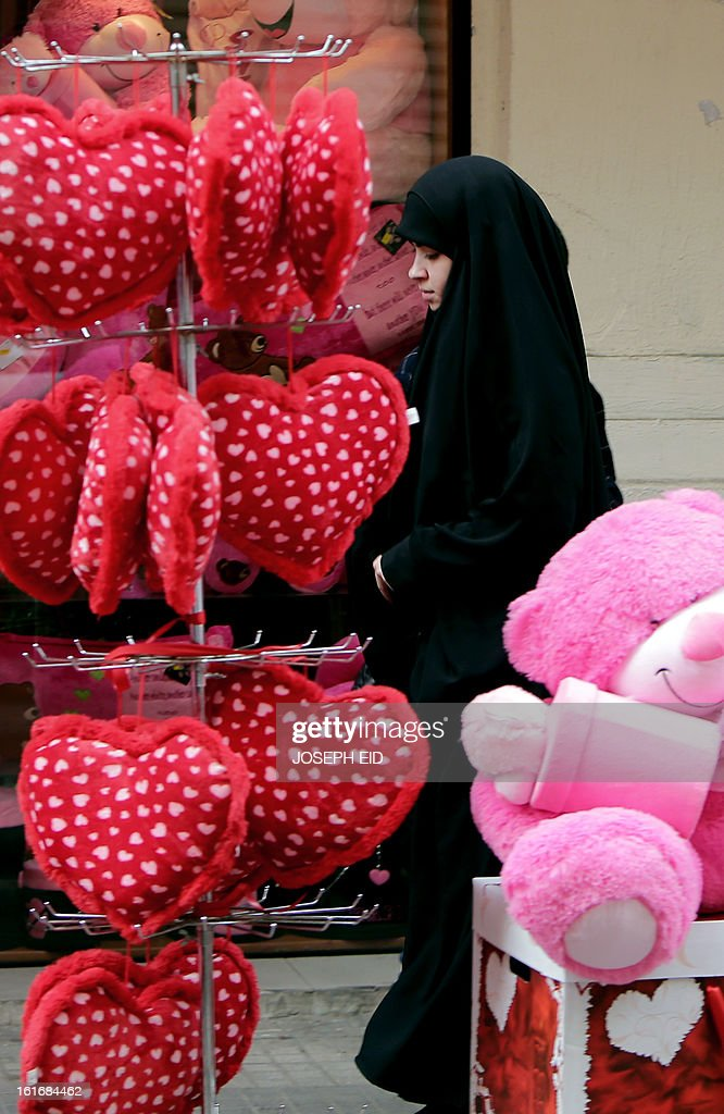A veiled girl walks past Valentine's Day gifts in the mainly Muslim Basta district of west Beirut on February 14, 2013. Valentine's Day is increasingly popular in the region as people have taken up the custom of giving flowers, cards, chocolates and gifts to sweethearts to celebrate the occasion. AFP PHOTO/JOSEPH