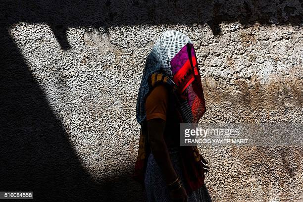 A veiled Indian woman walks on the street in Barsana some 130kms from New Delhi on March 16 2016 / AFP / François Xavier MARIT