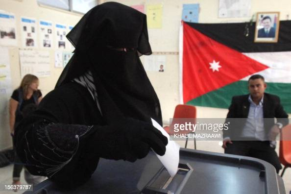 A veiled Jordanian woman casts her ballot at a polling station in Amman on November 9 in an early general election likely to produce MPs with tribal...