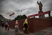 A veiled Muslim Uyghur woman walks passed a statue of Mao Zedong on July 31 2014 in Kashgar Xinjiang Uyghur Autonomous Region China Nearly 100 people...