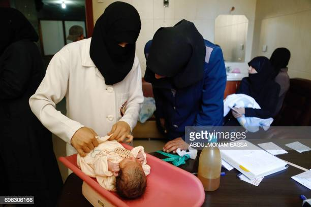 A veiled nurse gives childcare instructions to a new mother at a maternity clinic in the rebelheld town of Douma on the outskirts of the capital...