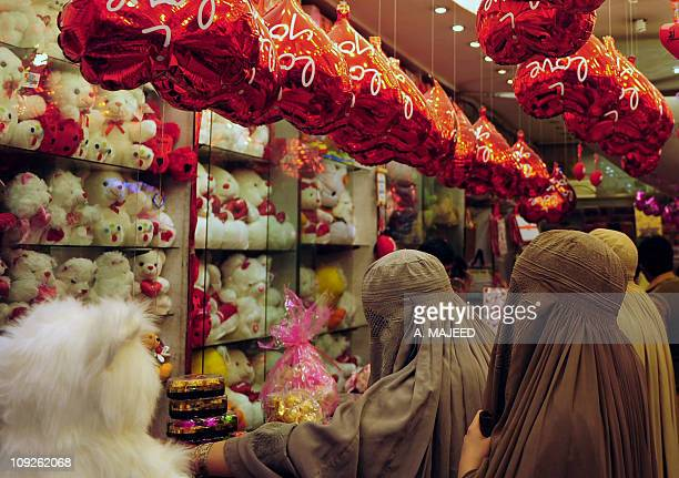 Veiled Pakistani women choose Valentine's Day gifts at a shop in Peshawar on February 11 2011 A number of shopping centers in Pakistan are full of...