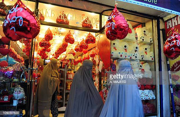 Veiled Pakistani women leave from a Valentine's Day gifts shop in Peshawar on February 11 2011 A number of shopping centers in Pakistan are full of...