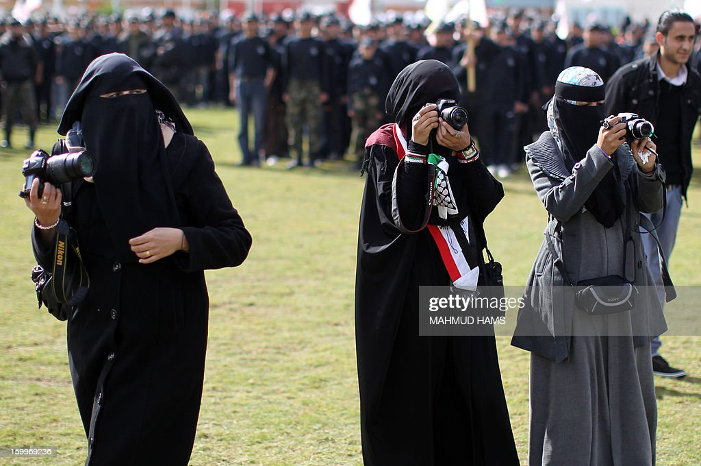 Veiled Palestinian photographers take pictures of a graduation ceremony for high-school students from a military school course organised by the Hamas security forces and the Hamas Minister of Education on January 24, 2013 in Gaza City.