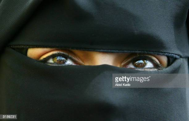 A veiled Palestinian woman looks on as she attends a protest March 30 2004 in Gaza City Gaza Strip Thousands of Palestinians attended the protest in...