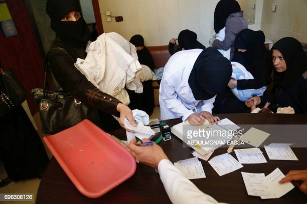 A veiled Syrian woman takes a receipt from a nurse at a maternity clinic in the rebelheld town of Douma on the outskirts of the capital Damascus...