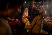 A veiled Uyghur woman sits at a food stall at a local market on August 1 2014 in Kashgar Xinjiang Uyghur Autonomous Region China Nearly 100 people...