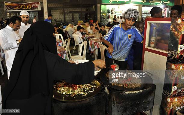 A veiled woman helps a young caterer prepare a traditional shreded meat dish at an outdoors restaurant in the heart of the Saudi Red Sea port of...