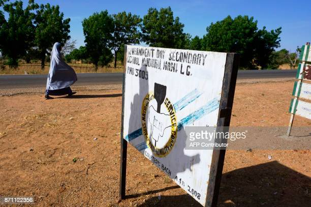 A veiled woman walks past a signpost of Government Day Secondary School in Muduru a rural district of Katsina state on November 3 2017 The 'Science...