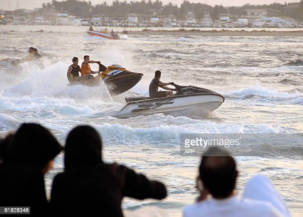 Veiled women and a man watch Saudi teenagers riding jet skis on the water in the Saudi city of Jeddah on the Red Sea coast on July 5 2008 The...
