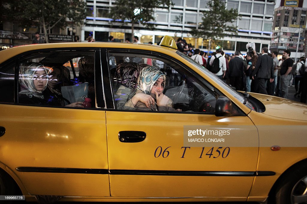Veiled women leave in a taxi as they flee clashes between protesters and riot police during a demonstration in the central Kizilay square in Ankara, on June 5, 2013. Thousands of striking workers took to the streets of Turkey's cities today, loudly joining calls for Prime Minister Recep Tayyip Erdogan to step down as mass protests against his rule intensified. Bellowing to the din of drums and wailing Turkish pipes, teachers, doctors, bank staff and others marched in a sea of red and yellow labour union flags in the capital Ankara and in Istanbul, where they converged on Taksim Square, the cradle of nearly a week of violent clashes.