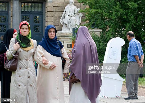 Veiled women walk past a symbolic knife that was installed on July 1 2010 in Dresden eastern Germany to commemorate the murder of a pregnant...