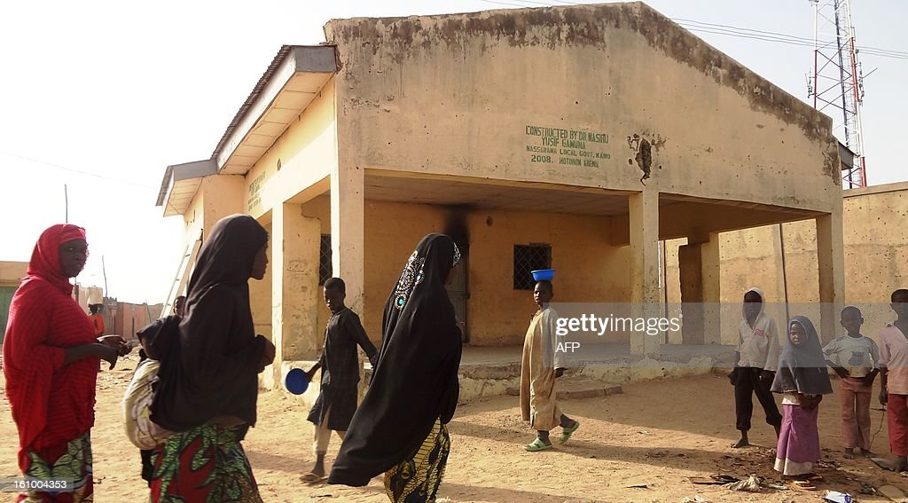 Veiled women walk past the Haye dispensary on February 8, 2013 in the northern Nigerian city of Kano, where gunmen on motorised tricycle killed seven female polio immunisation workers. Ten polio immunisation workers, nine of them women, were killed and five others injured in separate gun attacks on two polio clinics in the city. AFP PHOTO / Aminu ABUBAKAR