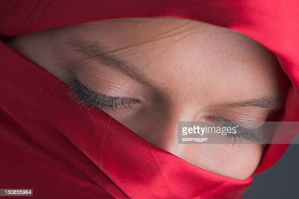 Veiled, young woman looking down