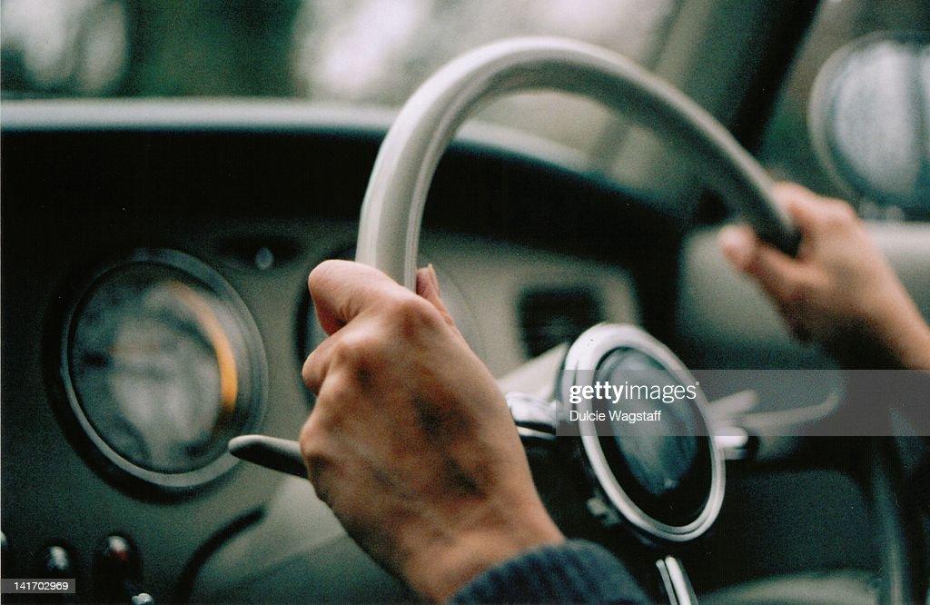 Veined hands driving vintage figaro car.