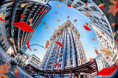 Fish eye view of the Velasca Tower in Milan, leaves are falling on the scene.