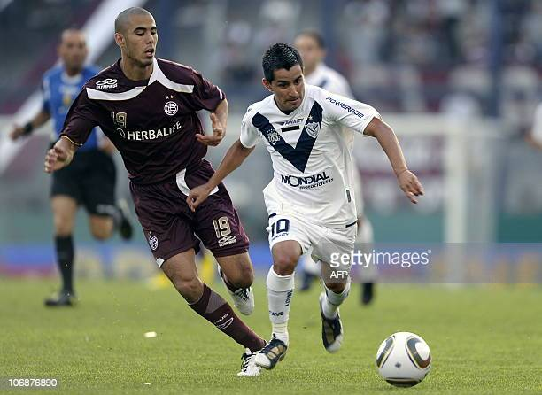 Velez Sarsfield's midfielder Maximiliano Moralez vies for the ball with midfielder Guido Pizarro of Lanus during their Argentina first division...