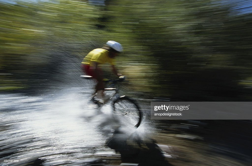 Motociclista em Velo watersplash : Foto de stock