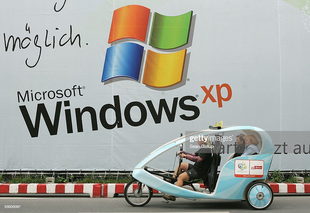 A velotaxi drives past a billboard advertising the Microsoft Windows XP operating system June 1 2005 in Berlin Germany Microsoft is locked in a legal...